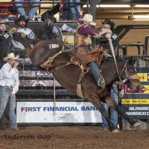 Cody DeMoss rides Lancaster and Jones' Total Equine Angel Fire for 87 points Friday night to take the lead in saddle bronc riding during the first performance of the San Angelo Stock Show and Rodeo. (PHOTO BY RIC ANDERSEN)