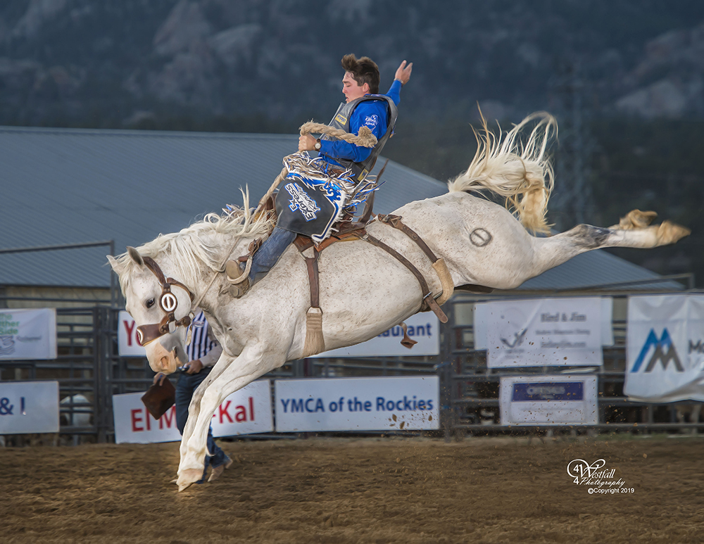Jake Wright rides Cervi Rodeo's Buckin' Crazy for 83.5 points to take the lead at Rooftop Rodeo on Wednesday night. Shortly after the ride, Wright was kicked in the head and had stitches to repair the gash. (PHOTO BY GREG WESTFALL)