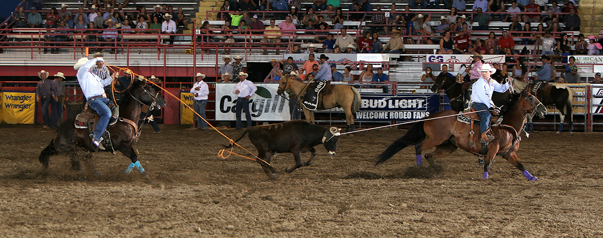 Garrett Tonozzi, right, and Dustin Davis stopped the clock in 5.7 seconds Thursday night to take the overall team roping lead at Dodge City Roundup Rodeo. (PHOTO BY DAVID SEYMORE)