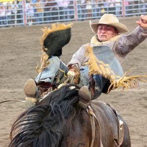 Will Lowe spurs Stace Smith's Cactus Black for 90 points Saturday night to win the first round of the Dodge City Roundup Rodeo and earn the right to compete for the championship Sunday during the championship round.