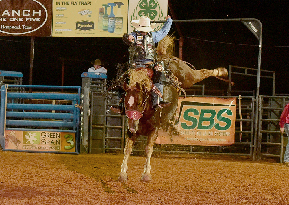 Bradley Harter rides Pete Carr Pro Rodeo's Life of Riley for 82 points Saturday night to share the saddle bronc riding victory at the Waller County Fair and Rodeo with brothers Jacobs and Sterling Crawley. (PHOTO BY DANIEL BECKENDORF)