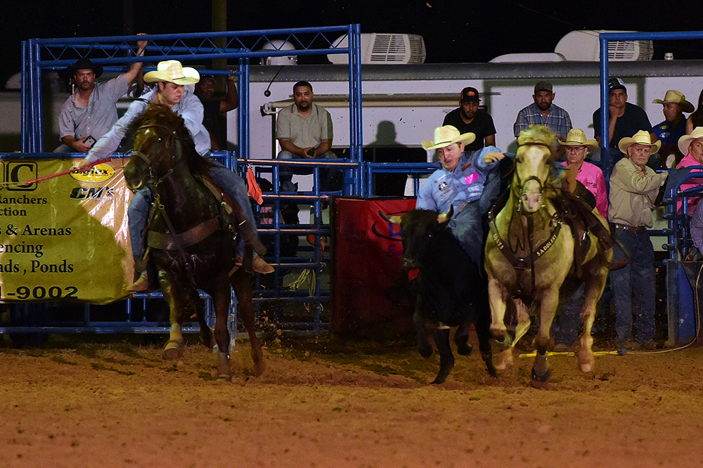 Dylan Schroeder transitions to his steer Thursday night en route a rodeo-leading, 4.2-second run. (PHOTO BY DANIEL BECKENDORF)