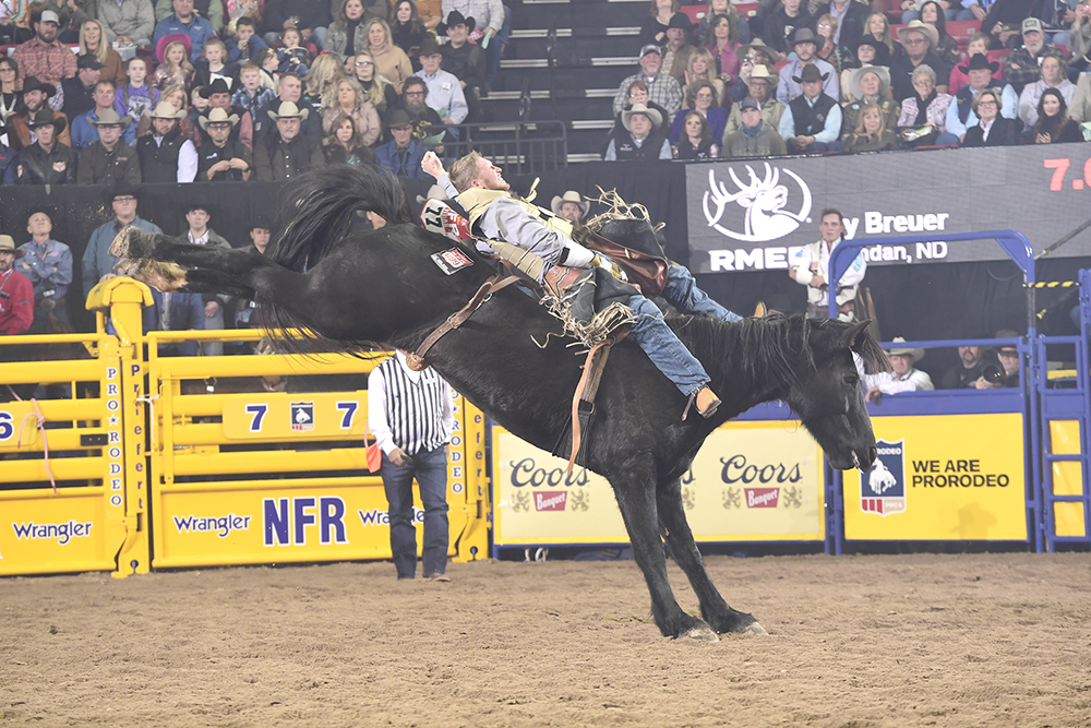 Ty Breuer rides Beutler & Son Rodeo's Black Kat for 87.5 points Friday night to finish in a tie for fourth place in the second round of the National Finals Rodeo. (PRCA PRORODEO PHOTO BY JAMES PHIFER)