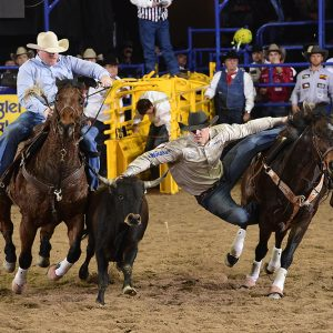 J.D. Struxness moves to his steer during his 4.3-second run Friday night to finish in a three-way tie for second place in the second round of the National Finals Rodeo. (PRCA PRORODEO PHOTO BY JAMES PHIFER)