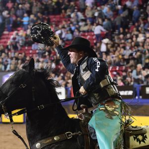Bull rider Garrett Smith rides a victory lap after winning Friday's second round of the National Finals Rodeo with a 91.5-point ride on Pete Carr's Black Gold. (PRCA PRORODEO PHOTO BY JAMES PHIFER)