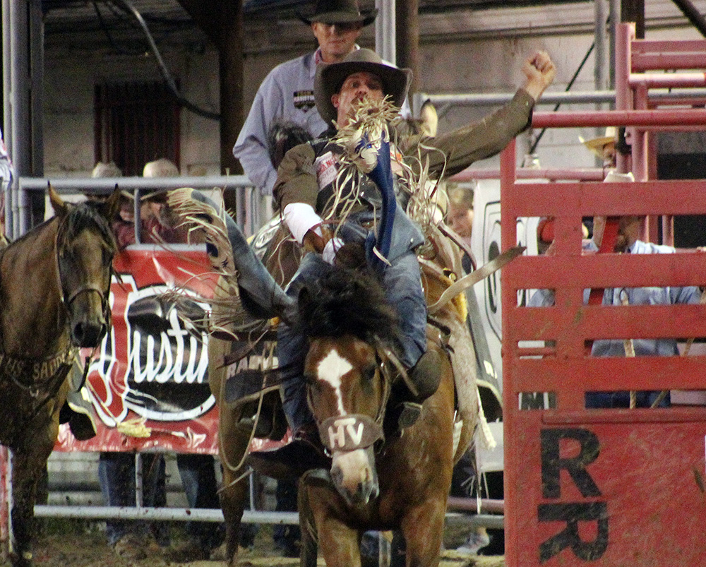 Orin Larsen rides Vold Rodeo's Spicey Chicken for 87 points to take the bareback riding lead after Wednesday's first performance of the Dodge City Roundup Rodeo.