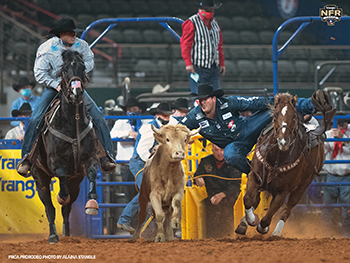 Jacob Edler transitions to his steer on his way to a 3.3-second run, which earned him a share of the Round 6 victory at the National Finals Rodeo. (PRCA PRORODEO PHOTO BY ALAINA STANGLE)