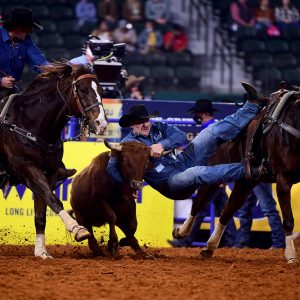 Tanner Brunner slides over to his steer during his 3.7-second run to finish second in Thursday's eighth round of the National Finals Rodeo. (PHOTO BY JAMES PHIFER)