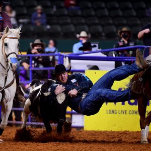 Jacob Edler transitions to his steer during his 3.9-second run, which helped him finish in a tie for fourth place in Wednesday's seventh round of the National Finals Rodeo. (PHOTO BY JAMES PHIFER)
