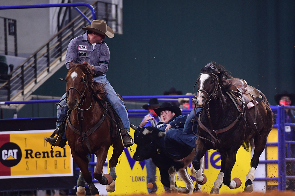 Jacob Edler transitions to his steer during a 4.0-second run, which helped him tie for fourth in Thursday's opening round of the National Finals Rodeo. (PHOTO BY JAMES PHIFER)