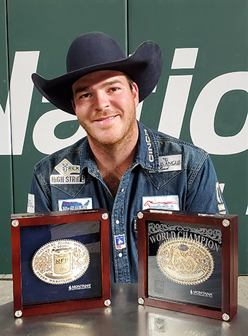 Jacob Edler poses with his average and world championship buckles Saturday night at the National Finals Rodeo. He also won two saddles and nearly $155,000 in 10 nights in Arlington, Texas.