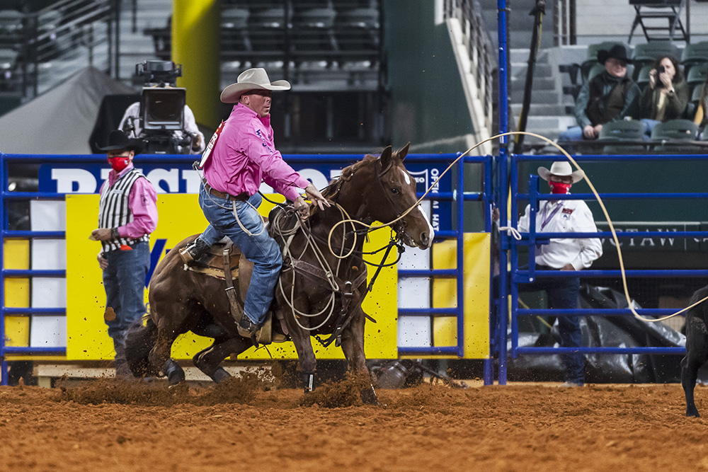 Ryan Jarrett dismounts his horse during his 8.2-second run Monday, which guided him to a third-place finish in the fifth round of the Wrangler National Finals Rodeo. (PHOTO BY JAMES PHIFER)