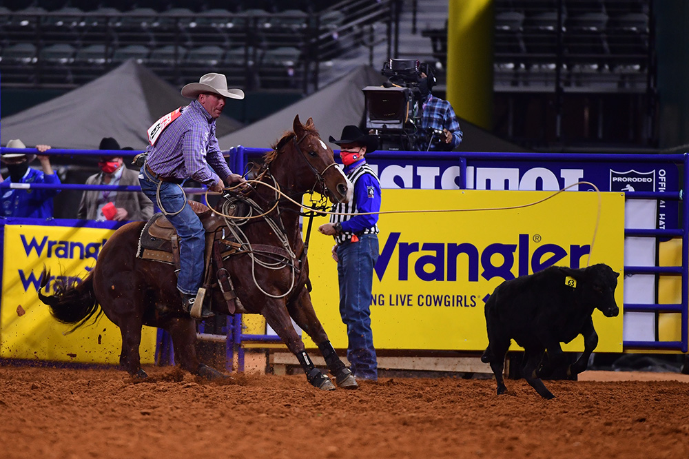 Ryan Jarrett dismounts his horse en route to a 7.8-second tie-down roping run to finish third in Thursday's eighth round of the National Finals Rodeo. (PHOTO BY JAMES PHIFER)